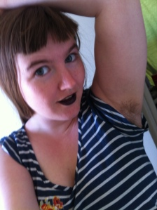 A young white woman in a stripey t-shirt and black lipstick smiles as she holds one arm over her head. Her armpits are unshaved.