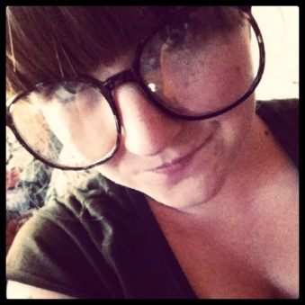A close up shot of the face of a white girl with thick bangs and very large glasses that take up half her face.