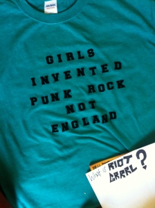 """A t-shirt with velvet lettering reading """"Girls invented punk rock not England."""" At the bottom, a piece of paper reads """"What is Riot Grrrl?"""""""