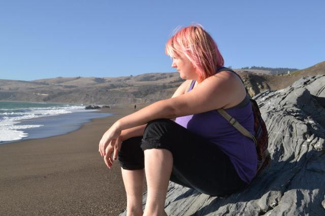 A photo of a white woman with pink hair sitting on a rock on a beach looking out toward the sea.