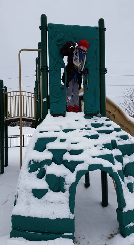 A photo of a woman, bundled in jackets, sweaters, scarf, sweatpants and a hat, standing on top of a snow-covered playground structure.